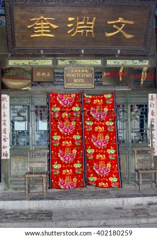 PINGYAO, CHINA - November 23. Tourist hotel with Chinese characters for the name of the hotel and traditional woolen curtains are used as front doors on November 23, 2014 in Pingyao. Unesco heritage.
