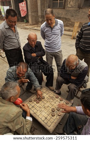 Pingyao,China - September 20, 2013 : Unidentified Chinese men play traditional Chinese checker on the streets of Pingyao