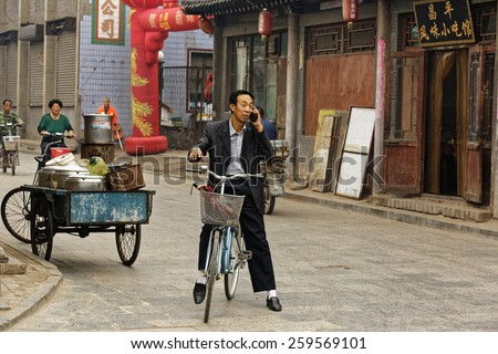 PINGYAO,CHINA - September 20,2013 : Unidentified chinese people  walk and shop on the ancient streets of Pingyao,China,whereas this man man talks on the mobile phone while he is on his bicycle