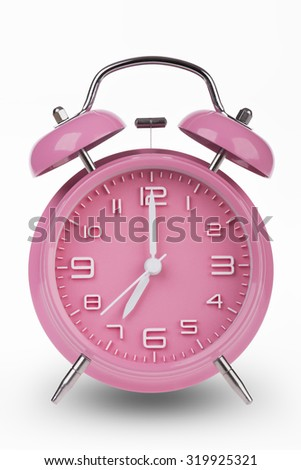 Pink alarm clock with the hands at 7 am or pm isolated on a white background.