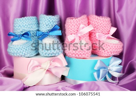 pink and blue baby boots and gifts on silk background