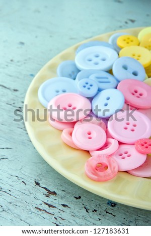 Pink and blue buttons on a light yellow plate on rustic wooden background