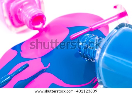 Pink and blue nail polish mix on the white background