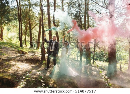 Pink and blue smoke in the hands of the newlyweds