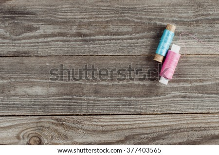 pink and blue thread reels on wooden background. - stock photo