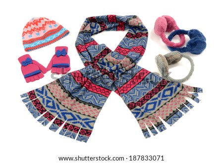 Pink and blue winter accessories isolated on white background. Cute wool scarf, a pair of gloves, a hat and earmuffs nicely arranged and matching. - stock photo