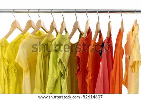 Pink and colorful casual shirts on wooden hangers, - stock photo