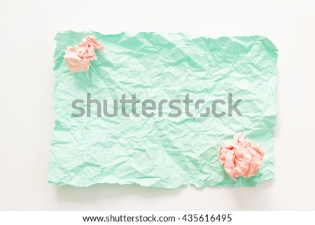 Pink and green crumpled paper texture on brown background.