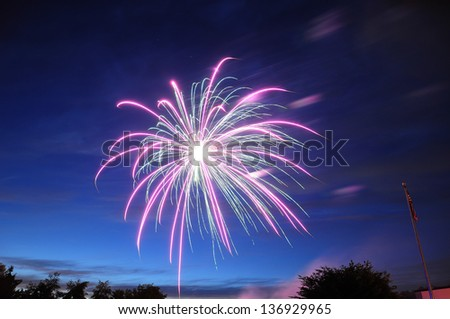 Pink and green firework on a midnight blue sky - stock photo