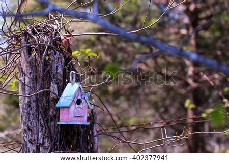 Pink and mint green birdhouse with butterfly hanging on old tree with foliage and barbed wire fence blurred in background - stock photo