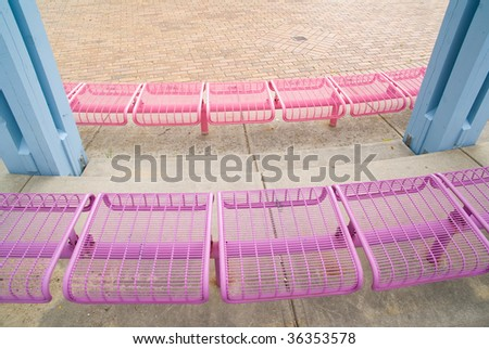 Pink and purple benches at a local garden - stock photo