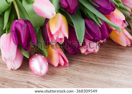 pink and purple easter tulips  with pink easter egg on wooden table  - stock photo