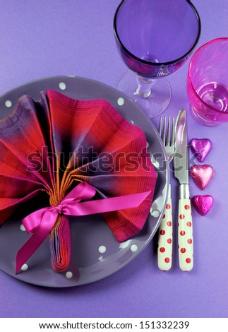 Pink and purple table setting with fan shape napkin and polka dot plate and cutlery with heart shape chocolates and pink & purple glasses for fun birthday or special occasion dining table. Vertical. - stock photo