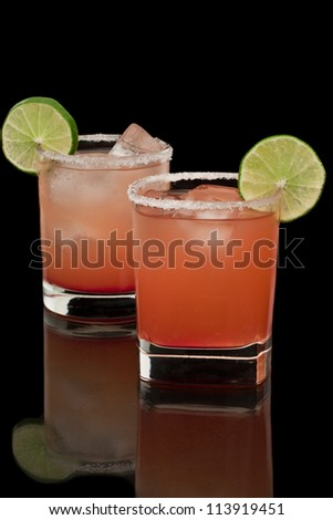 Pink and red drinks on a reflective surface with a salt rim and a lime garnish - stock photo