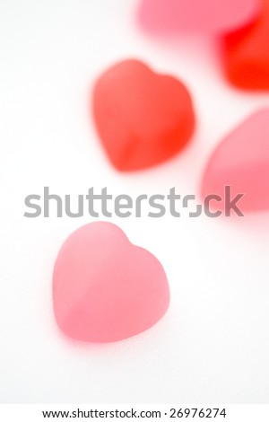Pink and red heart shaped jujubes on whit background
