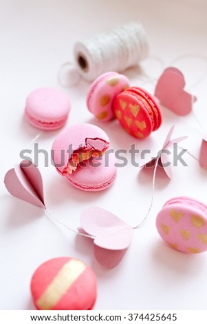 Pink and red macarons with paper hearts garland on a white background