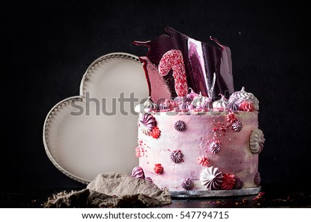 Pink and violet fancy birthday cake decorated with pink caramel, meringues, and marshmallows. Dark Rustic Style