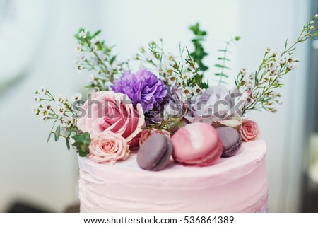 Pink and violet flowers and macaroons lie on top of tasty cake