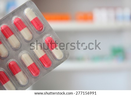 pink and white antibiotics capsules medicines pills blisters with drugstore shelves background - stock photo