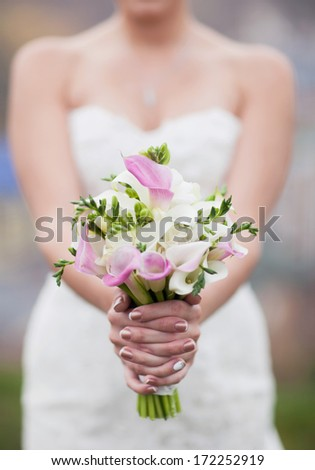 pink and white bridal bouquet of calla lilies in the hands of the bride - stock photo
