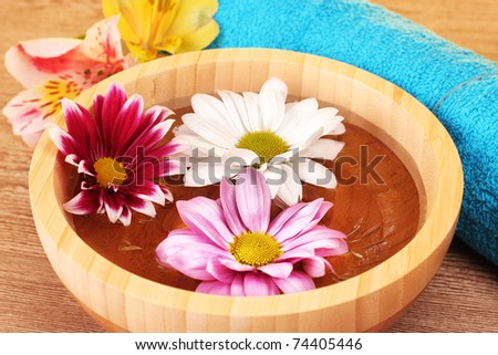 Pink and white flowers floating in bowl