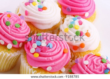 pink and white frosted cupcakes at an angle