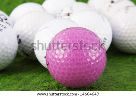 Pink and white golf balls on green - stock photo