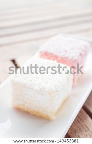 Pink and white lamington cakes on wood table, stock photo - stock photo