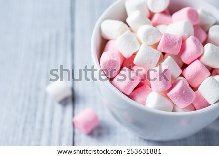 Pink and white marshmallows in a cup, over wood background.  - stock photo