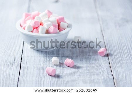 Pink and white marshmallows in bowl, over wood white background.  - stock photo