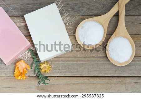 Pink and white natural soap spa with herbal powder scrub in spoon on wooden background. - stock photo