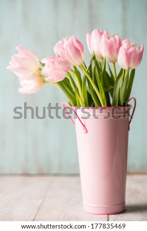 Pink and white pastel Tulips in a pink bucket vase - stock photo
