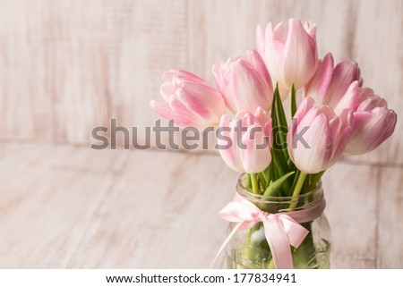 Pink and white pastel Tulips in glass vase room for text - stock photo