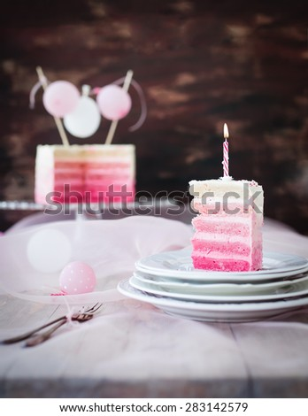 Pink and white piece of birthday cake with burning candle. Selective focus. - stock photo