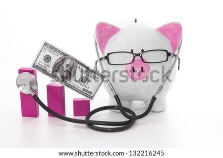 Pink and white piggy bank wearing glasses and stethoscope listening to graph model - stock photo