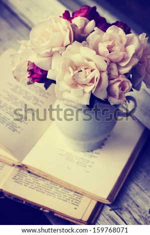 Pink and white roses and old books on wooden desk - stock photo