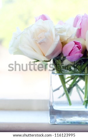 Pink and White Roses in Glass Vase in Windowsill - stock photo