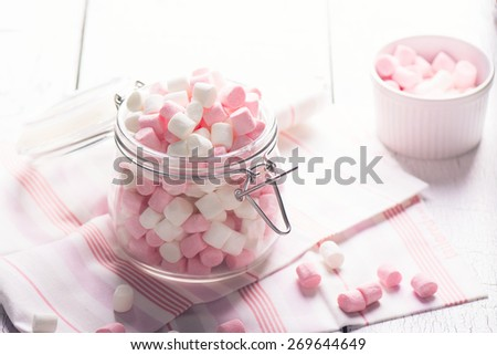 Pink and white small marshmallows in a glass pot on wooden table. Selective focus - stock photo