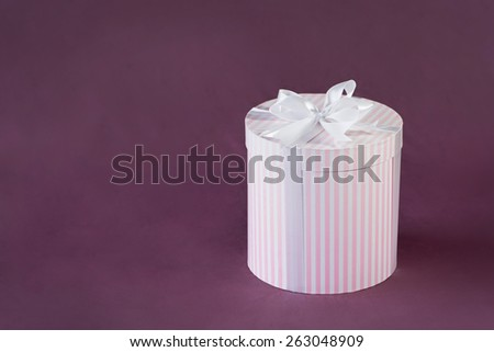 Pink and white striped gift box with white bow - stock photo