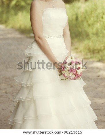 pink and white wedding bouquet of roses in the hands of the bride