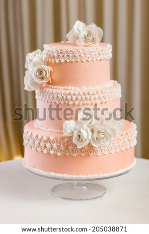 Pink and white wedding cake with individual decoration at withe table  - stock photo