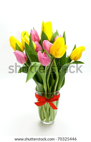 pink and yellow tulips in a glass tied with a red bow