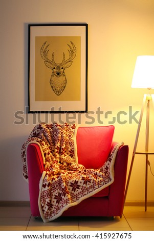Pink armchair with blanket and lamp on light wall background - stock photo