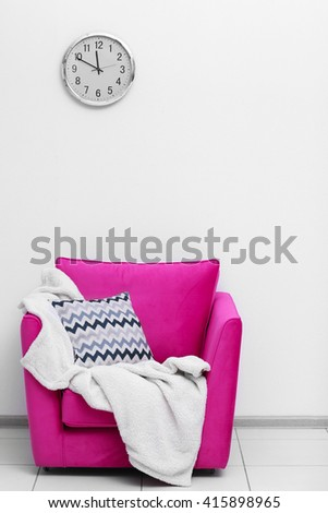Pink armchair with blanket and pillow on light wall background - stock photo