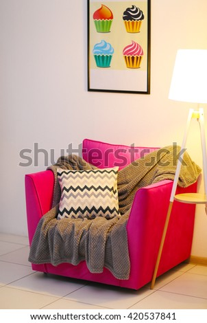 Pink armchair with blanket, pillow and lamp on light wall background