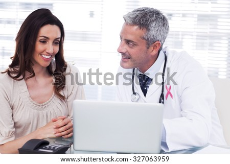 Pink awareness ribbon against docter showing something on laptop to his patient - stock photo