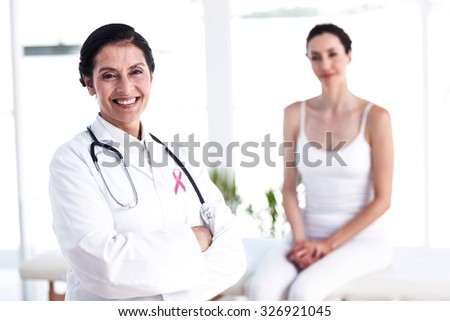 Pink awareness ribbon against doctor and patient smiling at camera - stock photo