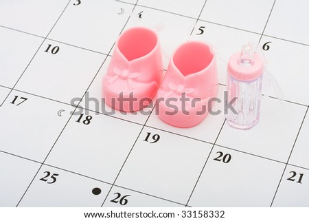 Pink baby booties and bottle on a calendar background, baby due date