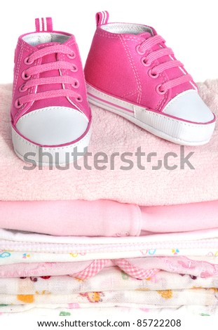 Pink baby booties on a pile of baby clothes - stock photo