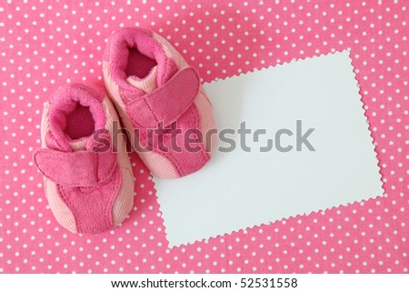 Pink baby shoes and blank note on spotted background - stock photo